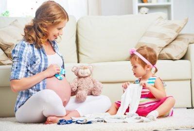gravida e menina preparam enxoval do bebe